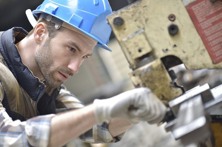 Industrial worker working on machine in factory-1