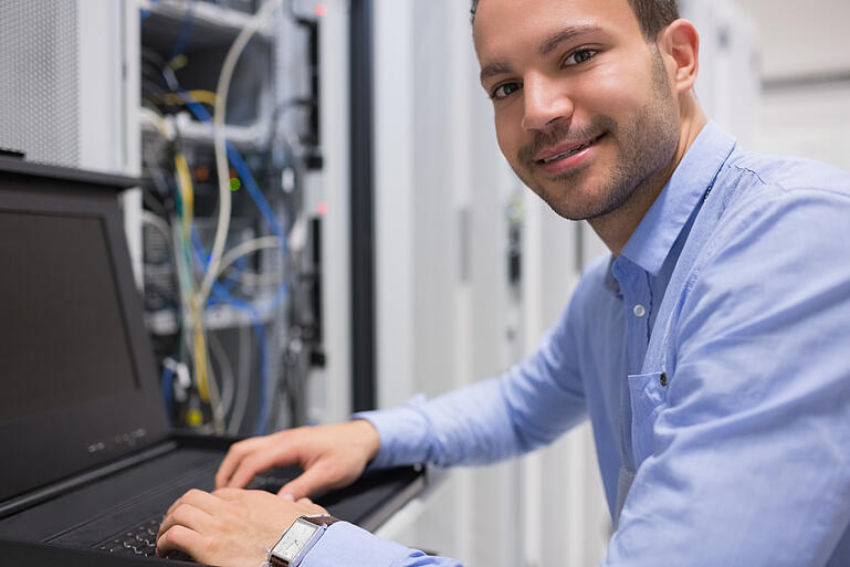 Man searching through servers in data center